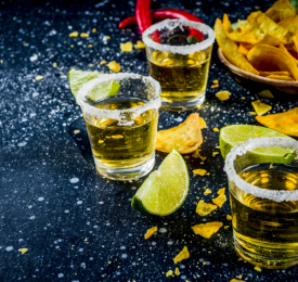 Shots of tequila with salt rim, limes and tortilla chips